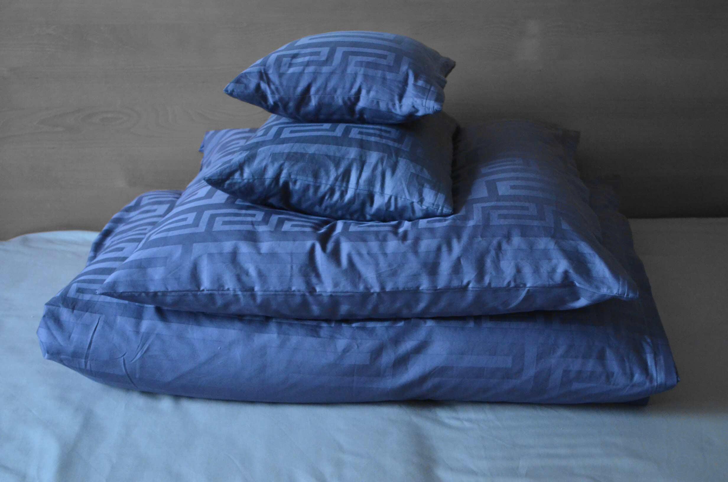 roetsch graue-selbst-genaehte-Bettwaesche-mit-gestapelten-Kissen