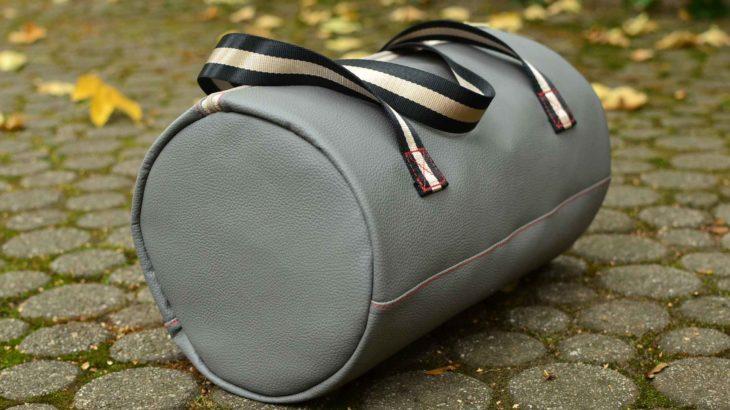 roetsch-seitenansicht-graue-kunstleder-sport-tasche-fuer-die-uni-auf-boden-stehend